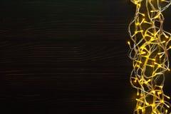 Christmas lights border on dark wooden background. Christmas lights background, copy space. Holiday shiny yellow garland border top view on dark wooden planks Stock Photos
