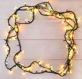Christmas lights background. Holiday glowing garland on light wo. Oden board. Winter holidays illumination, top view, flat lay royalty free stock image