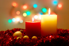 Christmas Lights. Christmas background with two burning candles, tinsel, golden balls and colorful lights Stock Images