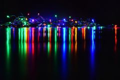 Christmas lights on black background with copy space. Colored reflecting surface. Stock Photography