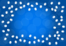 Christmas lights on blue background with space for text Royalty Free Stock Photos