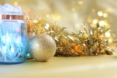 Christmas lights in jar on gold bokeh lights background Royalty Free Stock Photos