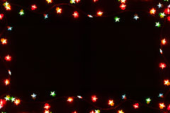 Christmas lights border on black background. Christmas lights stars frame on black background. Holiday shiny garland border with copy space, top view. Xmas tree royalty free stock photos