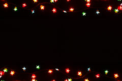 Christmas lights border on black background. Christmas lights stars frame on black background. Holiday shiny garland border with copy space, top view. Xmas tree stock image