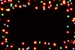 Christmas lights border on black background. Christmas lights stars frame on black background. Holiday shiny garland border with copy space, top view. Xmas tree stock photography