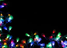 Christmas lights border on black background. Christmas lights string border on black background. Holiday shiny neon led garland top view. Xmas tree decorations royalty free stock photo