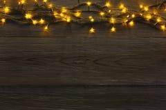 Christmas lights border on grey wooden background. Christmas lights background, copy space. Holiday shiny garland border top view on dark grey wooden planks Stock Photo