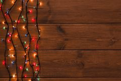 Christmas lights border on wood background. Christmas lights background, copy space. Holiday shiny colorful garland border top view on brown wooden planks Royalty Free Stock Images