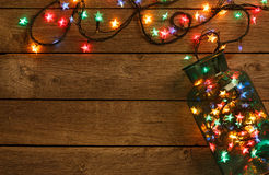 Christmas lights border on wood background. Christmas lights background. Holiday shiny garland border spread from glass jar, top view on brown wooden planks stock images
