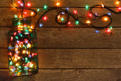 Christmas lights border on wood background. Christmas lights background. Holiday shiny garland border spread from glass jar, top view on brown wooden planks stock image