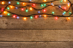 Christmas lights border on wood background. Christmas lights background. Holiday shiny garland border top view on light brown wooden planks surface. Xmas tree royalty free stock image