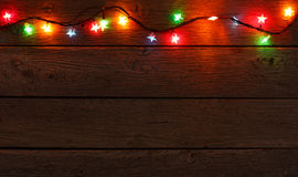 Christmas lights border on wood background. Christmas lights background. Holiday shiny garland border top view on light brown wooden planks surface. Xmas tree Royalty Free Stock Photos
