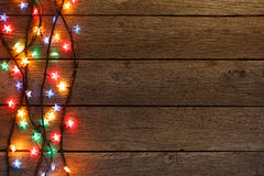 Christmas lights border on wood background. Christmas lights background. Holiday shiny garland border top view on light brown wooden planks surface. Xmas tree stock image