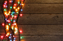 Christmas lights border on wood background. Christmas lights background. Holiday shiny garland border top view on light brown wooden planks surface. Xmas tree stock photo