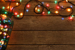 Christmas lights border on wood background. Christmas lights background. Holiday shiny sparkling star garland border spread from glass jar, top view on brown Royalty Free Stock Photos
