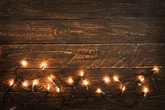 Christmas lights bulb on wood table. Merry christmas xmas background. topview, border design - rustic and vintage styles Royalty Free Stock Image