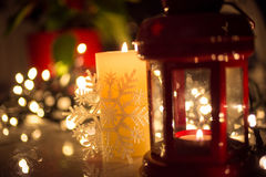 Christmas lights, burning candle and vintage lantern on table Royalty Free Stock Images