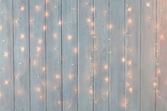 Christmas lights burning on a white wooden background. New Year back. Stock Photos