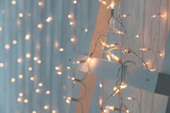 Christmas lights burning on a white wooden background. New Year back. Royalty Free Stock Images