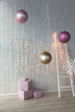 Christmas lights burning on a white wooden background with pink giftboxes and stairs Royalty Free Stock Images