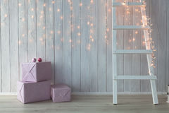 Christmas lights burning on a white wooden background with pink giftboxes and stairs Royalty Free Stock Photos
