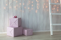 Christmas lights burning on a white wooden background with pink giftboxes and stairs Stock Image