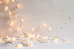 Christmas lights burning  on a white wooden background. Royalty Free Stock Photo
