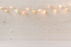 Christmas lights burning  on a white wooden background. Xmas background Royalty Free Stock Images