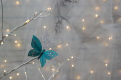 Christmas lights and butterfly. Light blue jewelled butterfly on white tree branch with Christmas lights and neutral white background Royalty Free Stock Photos