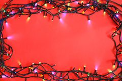 Christmas lights on color background, top view. Glowing Christmas lights on color background, top view royalty free stock images