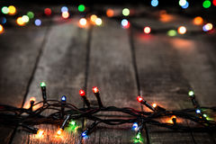 Christmas lights on dark wooden background Stock Image