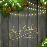 Christmas lights and decorations on black wooden background. Holiday lettering Merry Christmas and Happy New Year on black wooden background with winter Stock Photo
