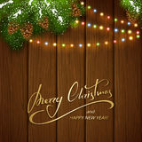 Christmas lights and decorations on brown wooden background. Holiday lettering Merry Christmas and Happy New Year on brown wooden background with winter Stock Image