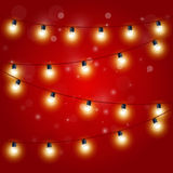 Christmas Lights - festive carnival garland with light bulbs. On red Royalty Free Stock Images