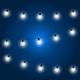 Christmas Lights - festive light bulbs garland. On blue Royalty Free Stock Photos