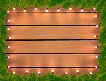 Christmas lights with fir twigs, wooden background. Illustration Royalty Free Stock Photography