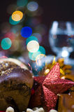 Christmas lights and food. A closeup of Christmas cake with blurred colored lights and tableware in the background Royalty Free Stock Photography