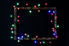 Christmas lights in a frame on black background. Holiday time. royalty free stock photo