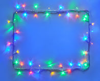 Christmas lights frame on blue background with copy space. stock photography