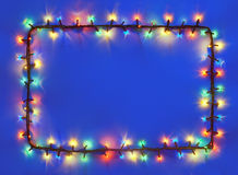 Christmas lights frame on dark blue background. With copy space. Decorative garland royalty free stock photography