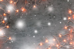 Christmas lights frame on dark grey stone background. With snow, copyspace stock photography
