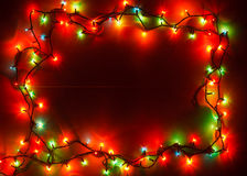 Christmas lights frame. Christmas lights of different colors frame on wooden planks stock images