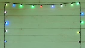 Christmas lights frame. Garland on a wood background stock video footage
