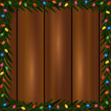 Christmas lights frame. Square frame made of colorful Christmas lights and fir branch on a wooden background Royalty Free Stock Image