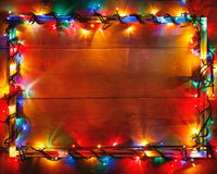 Christmas lights frame on wooden background royalty free stock image