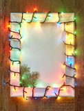 Christmas lights frame on wooden background Stock Photography