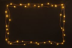 Christmas lights garland border over black background. Flat lay, copy space. Christmas lights garland border over black background. Flat lay, copy space royalty free stock photography