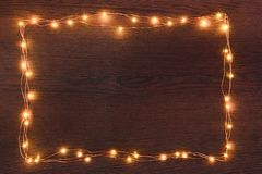 Christmas lights garland border over dark wooden background. Flat lay, copy space. Christmas lights garland border over dark wooden background. Flat lay, copy stock photography