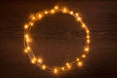 Christmas lights garland circular border over dark wooden background. Flat lay, copy space. Christmas lights garland circular border over dark wooden background stock photos