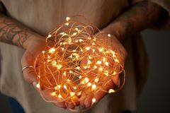 Christmas lights garland in female hands stock image